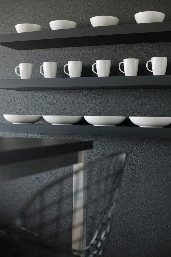 Un mur et des étagères noirs subliment une collection de céramiques blanches
