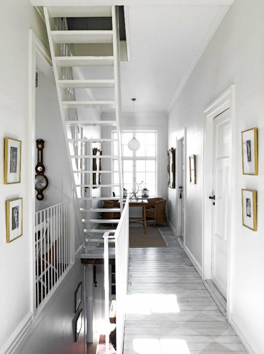 Dans cet appartement, l'entrée mène à un petit coin détente avec des meubles en osier