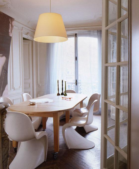 Des chaises Panton ornent une table de repas en bois brut