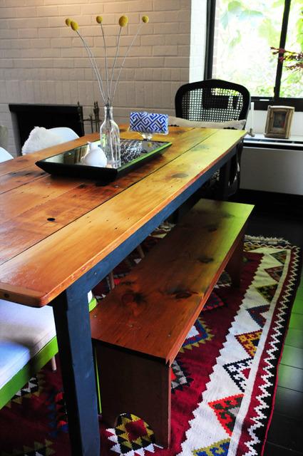 Table en bois brut, banc vintage et tapis imprimé navajo