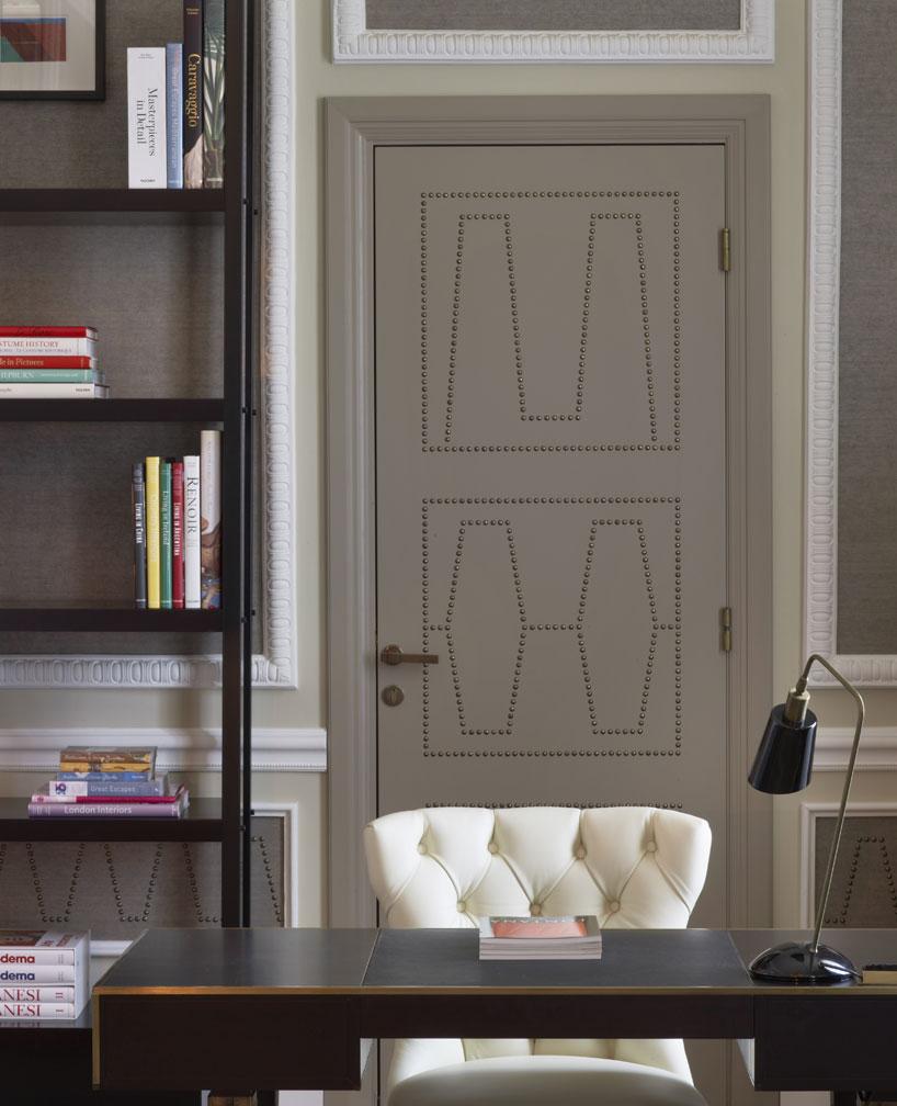 Des motifs en clous de tapissier recouvrent les murs et les portes
