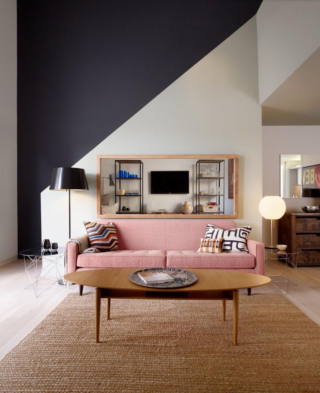 Canapé rose dans un séjour en noir bois et blanc
