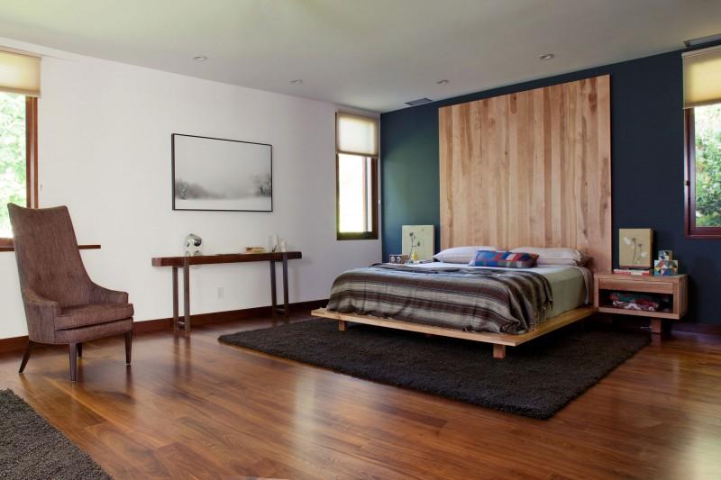 Tête de lit en bois massif et mur peint en bleu pétrole