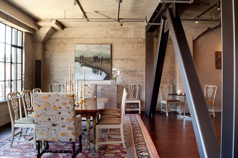 Loft avec poutres apparentes en acier, structure en béton brut et verrières