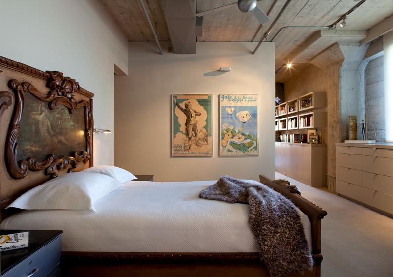 Tête de lit en bois sculptée en meubles de rangements contemporains côtoient le style industriel du loft