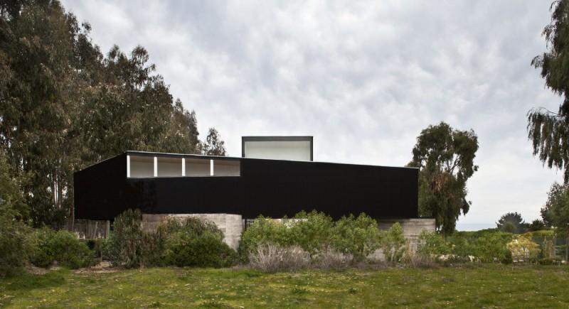 Une maison contemporaine en bois noir et béton brut