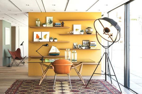 Ambiance vintage avec ce mur jaune et du mobilier Carlo Mollino