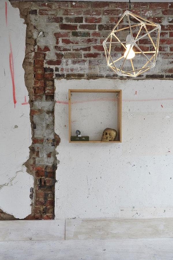 Mur en briques rouges et luminaire géométrique