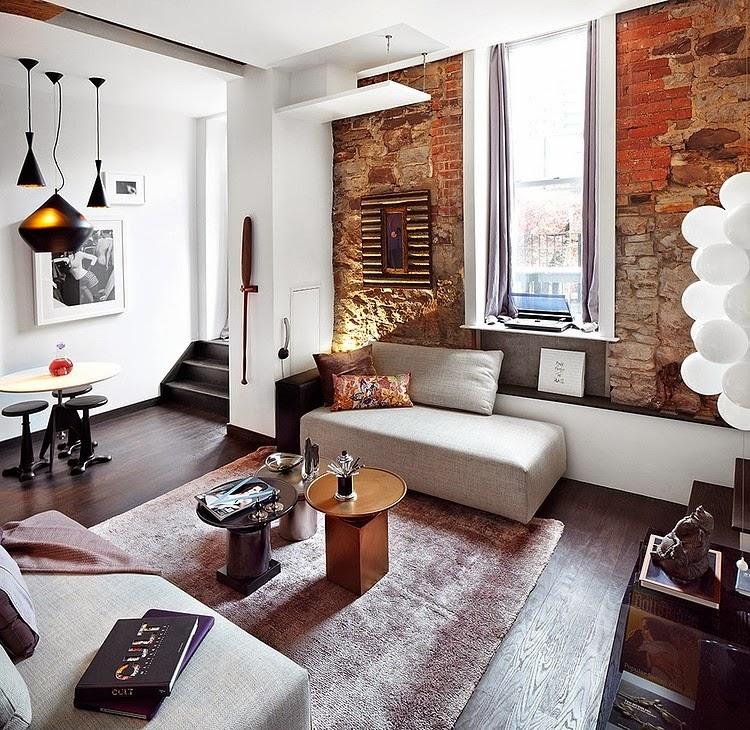 Loft avec luminaires Tom Dixon et murs en briques rouge