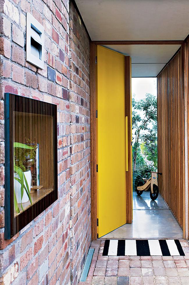 Porte jaune et mur en briques rouge