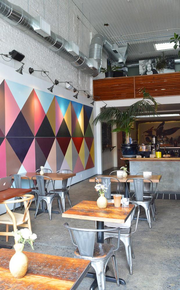 Loft avec mur en briques blanches, chaises Tolix et lampes industrielles