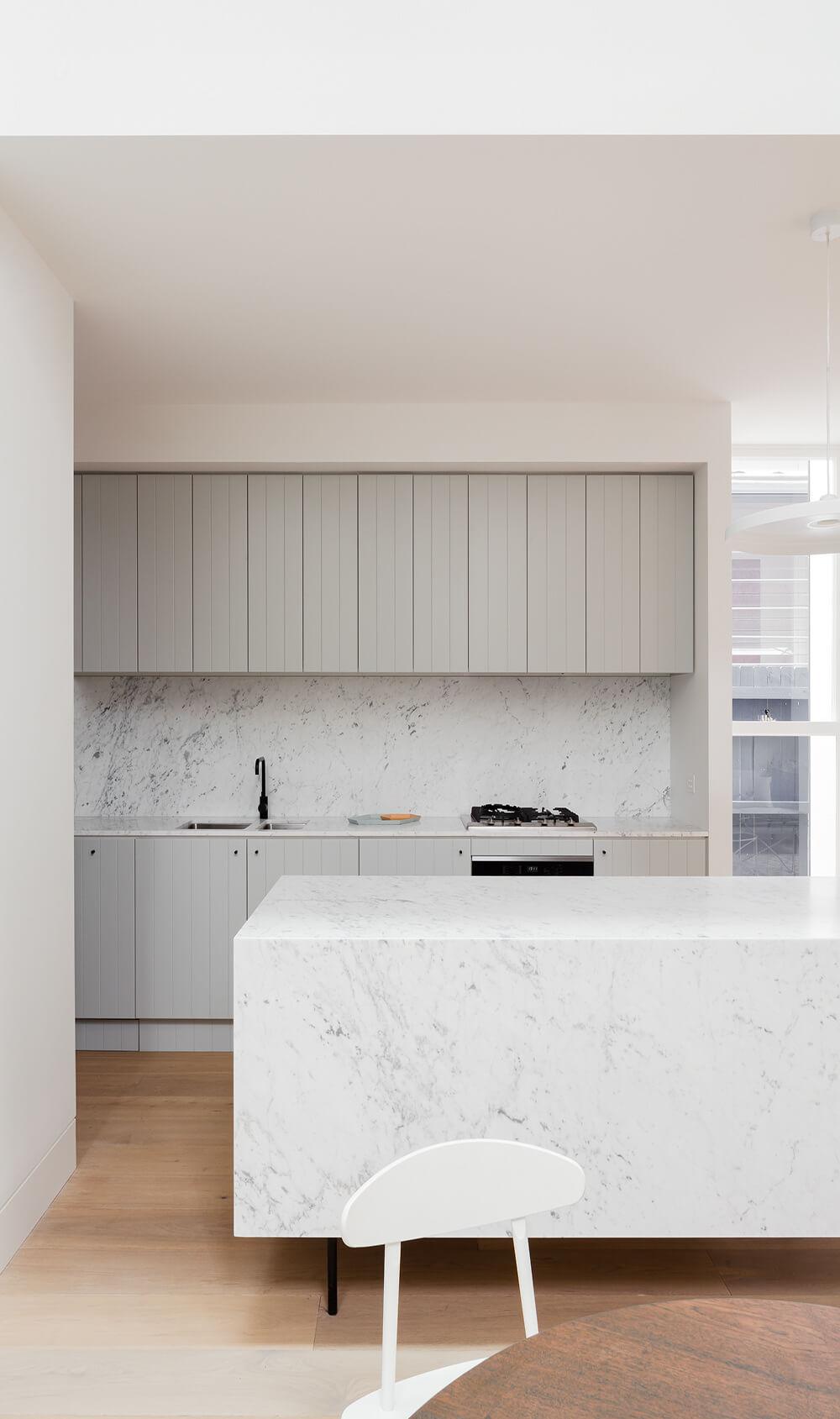 Cuisine avec un îlot central en marbre et meubles en bois gris