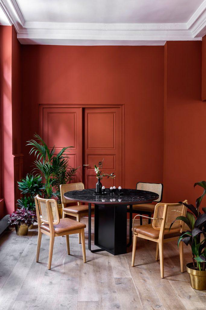Salle à manger avec table noire et chaises en cannage