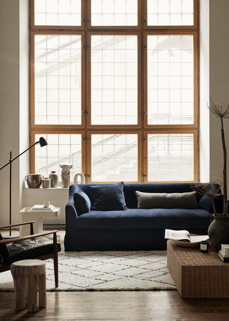 Décoration salon cosy avec tapis berbère et canapé en velours bleu