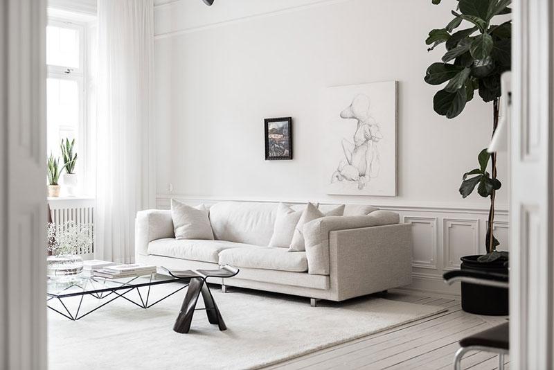 Salon avec un canapé blanc et du parquet blanc
