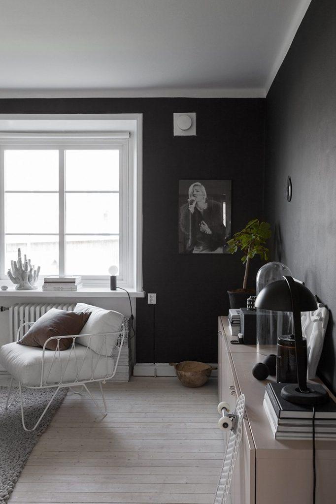 Salon cosy avec du parquet blanc et des murs noirs